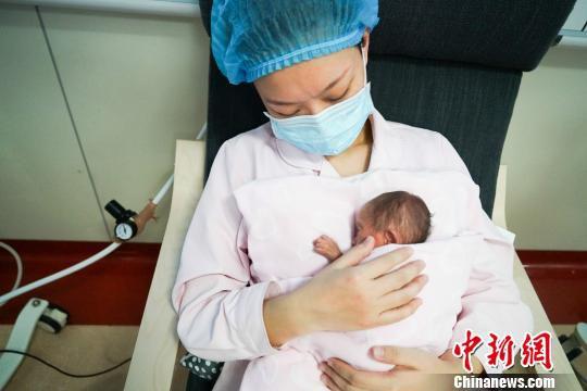 """图为重庆市妇幼保健院的新生儿科护士万华正在新生儿科的住院患儿进行""""袋鼠式护理""""。 向雅诗 摄"""