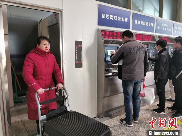 谢里千推着行李箱奔走在各个自动售取票机之间 韩章云 摄