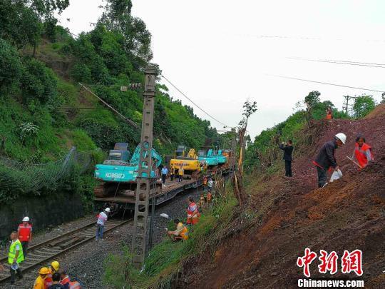 5月22日19时许,随着溜坍泥石的清挖基本结束,铁路部门将重型机械装车运回,采用人工清挖和检修的方式对线路进行开通前的最后工作。 钟欣 摄