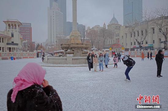 2月12日,市民及游客在雪中的天津意式风情街马可波罗广场拍照游玩。当天,天津迎来2019年首场降雪。中新社记者 佟郁 摄